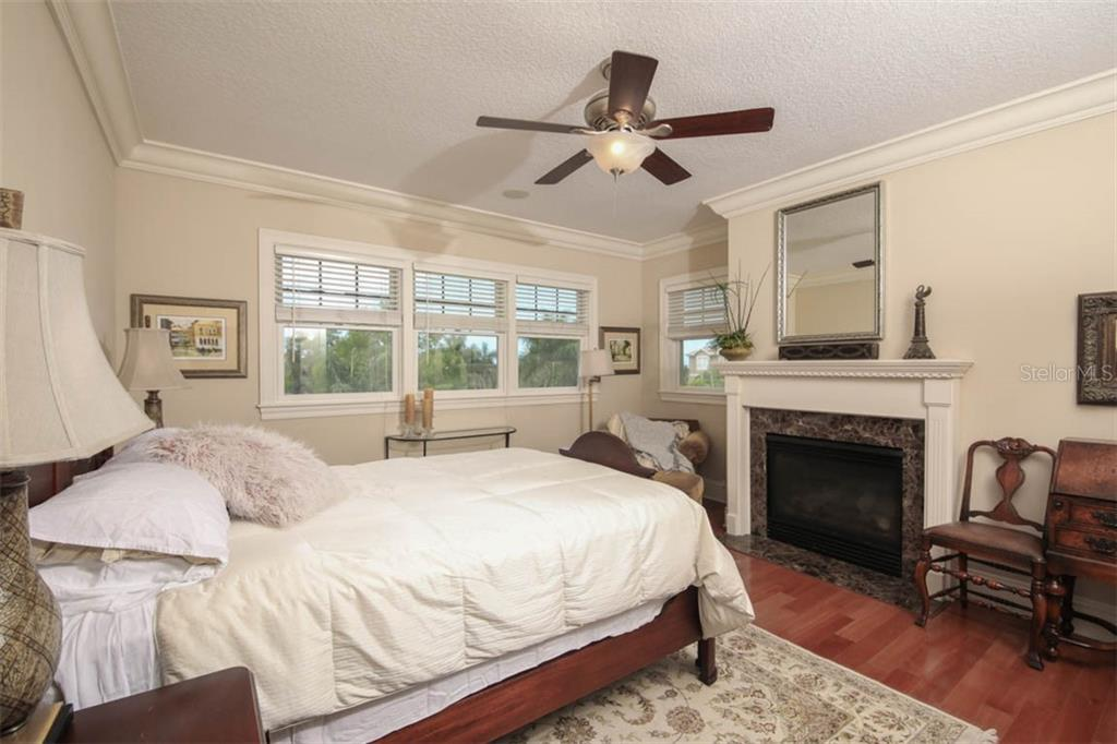 Master bedroom with gas fireplace. - Single Family Home for sale at 7153 Hawks Harbor Cir, Bradenton, FL 34207 - MLS Number is A4434661