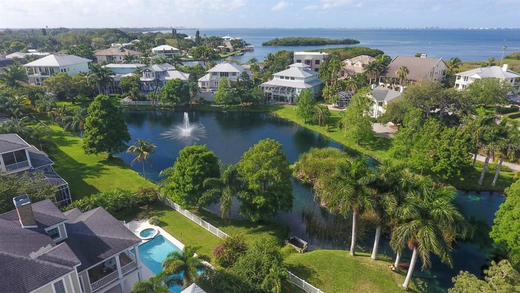 Aerial view of the backyard pool, pond view and Sarasota Bay beyond. - Single Family Home for sale at 7153 Hawks Harbor Cir, Bradenton, FL 34207 - MLS Number is A4434661