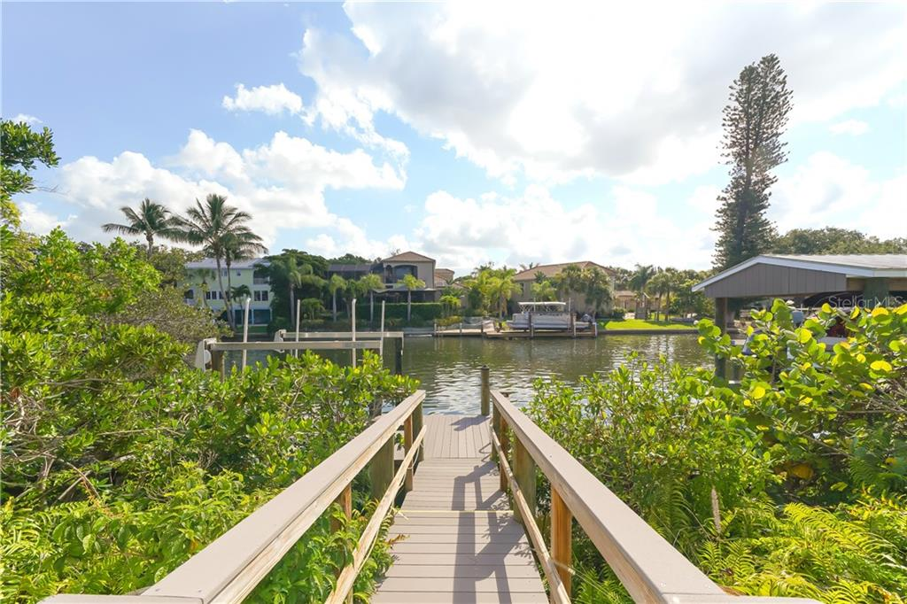 The tropically landscaped fenced pool, leads to a deepwater dock with a 7000 lb lift plus a ladder for easy access to kayaking and paddle boating. - Single Family Home for sale at 5143 Oxford Dr, Sarasota, FL 34242 - MLS Number is A4434790