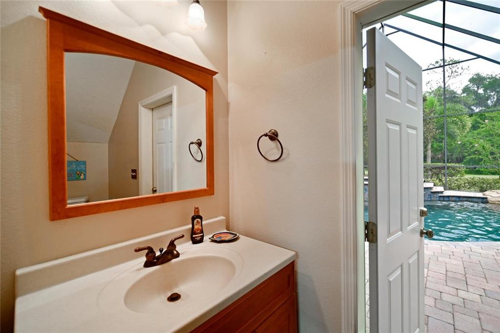 Half bath in garage with access to pool - Single Family Home for sale at 13825 18th Pl E, Bradenton, FL 34212 - MLS Number is A4435082