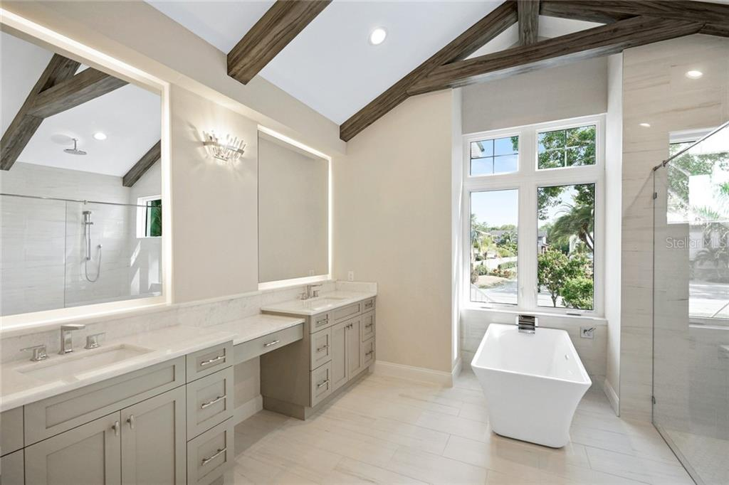 Master bathroom with vaulted ceilings and hand painted faux wood beams, large shower, double sink vanity - Single Family Home for sale at 1555 Sandpiper Ln, Sarasota, FL 34239 - MLS Number is A4436047