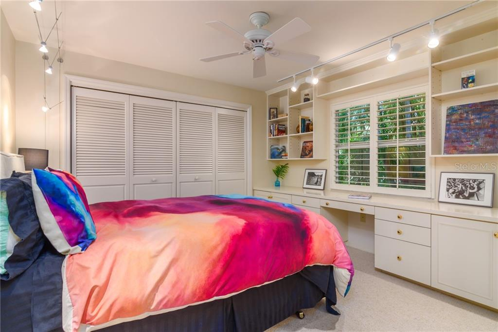 Bedroom w/ built-in desk, bookshelves, plantation shutters & view of the tropical backyard - Single Family Home for sale at 8511 Heron Lagoon Cir, Sarasota, FL 34242 - MLS Number is A4439489