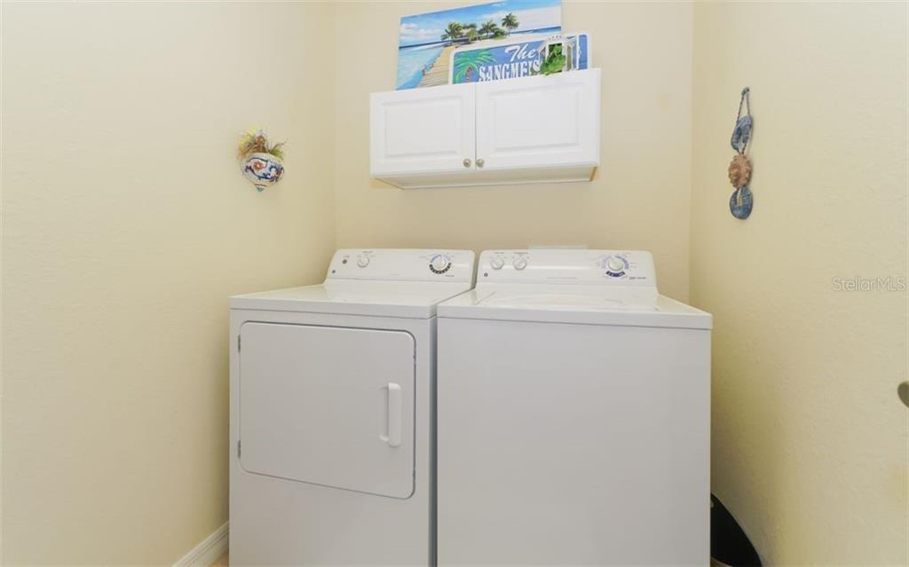 Laundry room with cabinet storage above adjacent to bonus room. - Condo for sale at 200 San Lino Cir #233, Venice, FL 34292 - MLS Number is A4440138