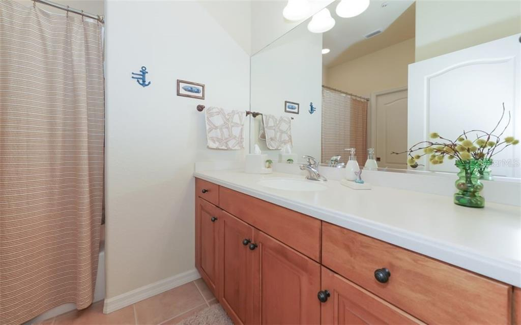 Guest bath with large vanity, corian counters and tub/shower combination. - Condo for sale at 200 San Lino Cir #233, Venice, FL 34292 - MLS Number is A4440138