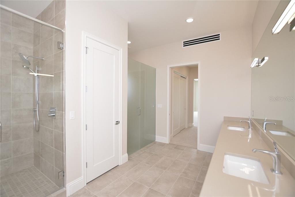 Tile shower, large linen closet and etched glass door to private water closet. - Condo for sale at 609 Golden Gate Pt #202, Sarasota, FL 34236 - MLS Number is A4441802