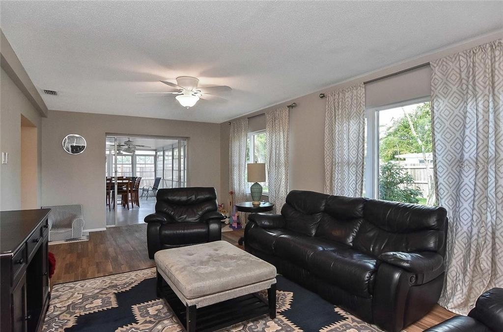Family room with sliders to lanai - Single Family Home for sale at 105 Alba St E, Venice, FL 34285 - MLS Number is A4446473