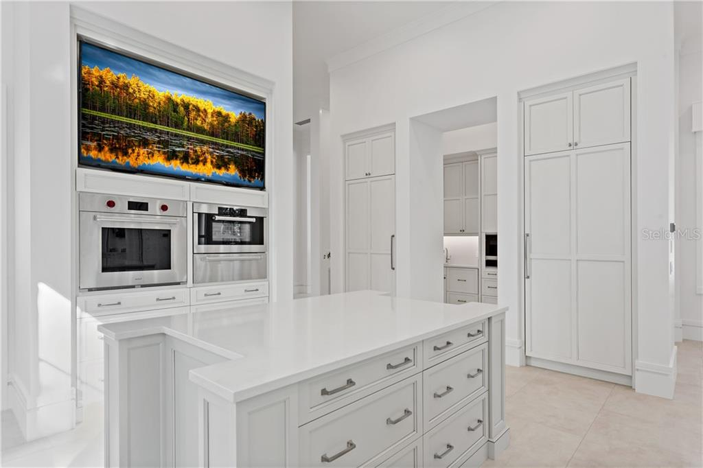 From here you can see the full sized Sub-Zero refrigerator and freezer, all fully finished with custom cabinetry. Also note the service pantry easily accessed from the kitchen. - Single Family Home for sale at 552 Eagle Watch Ln, Osprey, FL 34229 - MLS Number is A4454431