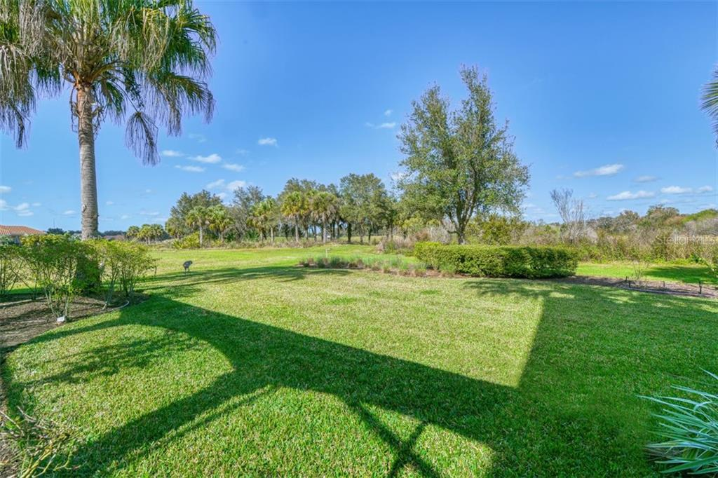 Just visible is the golf course green #1 behind the palms - Single Family Home for sale at 3719 Founders Club Dr, Sarasota, FL 34240 - MLS Number is A4455099