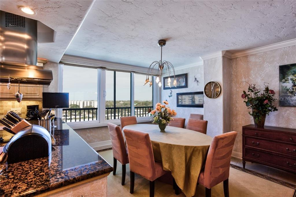 Dining area is part of the gourmet kitchen space and features include crown moulding - Condo for sale at 5880 Midnight Pass Rd #911, Sarasota, FL 34242 - MLS Number is A4462559