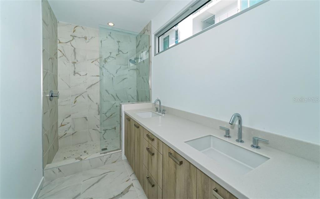 Natural light glass enclosure. Solid surface counter tops and dual vanities with modern fixtures create a crisp clean owners bath ambiance. - Condo for sale at 1350 5th Street #104, Sarasota, FL 34236 - MLS Number is A4463799