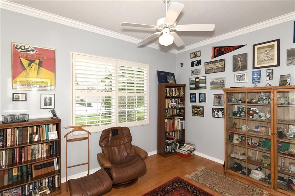 Guest bedroom, wood flooring, crown molding, plantation shutters - Villa for sale at 4590 Samoset Dr, Sarasota, FL 34241 - MLS Number is A4471881