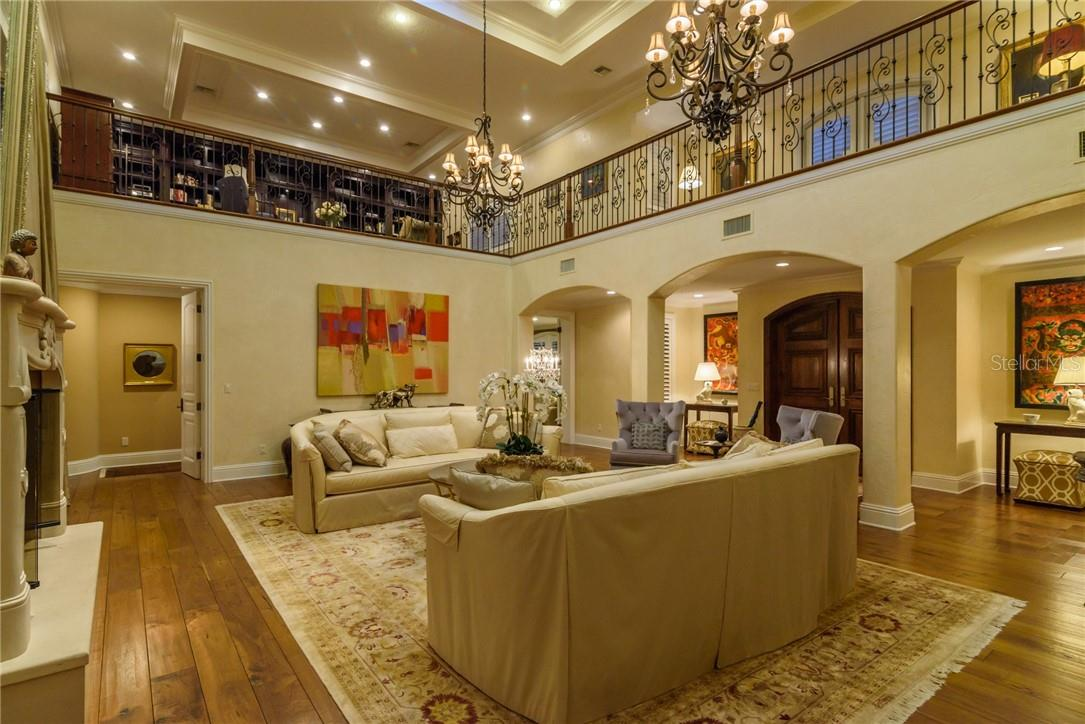 A Grand Foyer featuring custom wide plank walnut flooring blossoms into a two story elegant living room with loads of seating and a crackling fireplace beckoning. - Single Family Home for sale at 1807 Oleander St, Sarasota, FL 34239 - MLS Number is A4475067