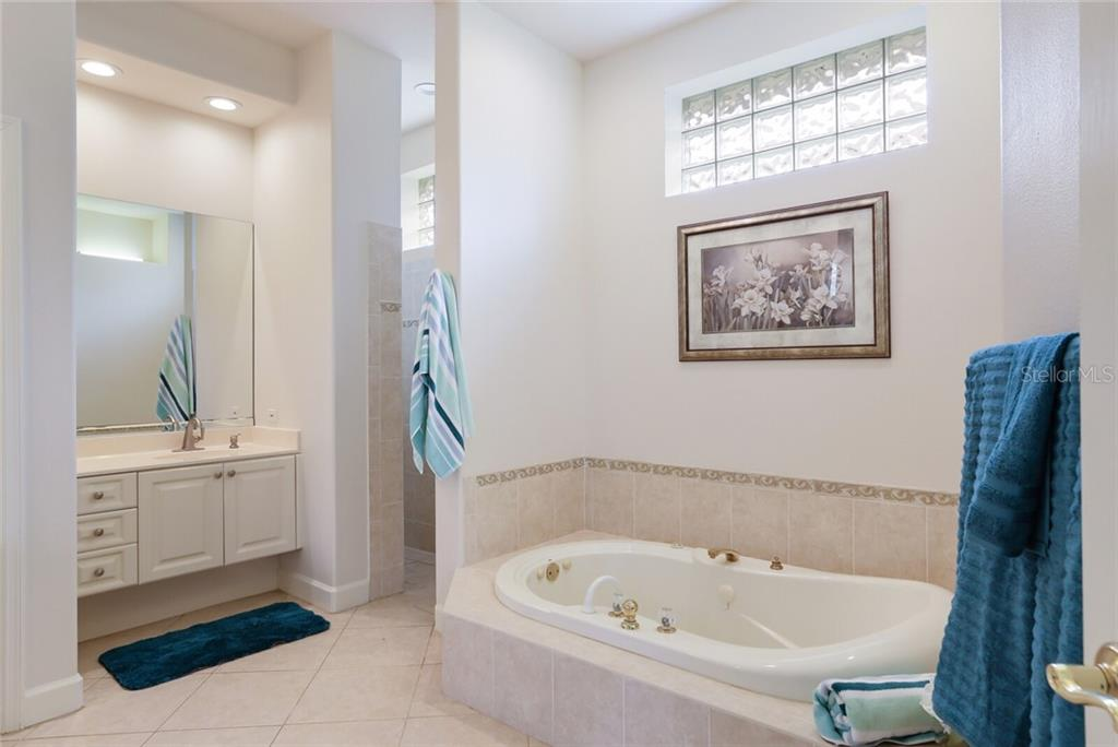 The master bath features two sinks, a soaking tub, a water closet and a walk-in, zero-entry shower. - Single Family Home for sale at 9618 53rd Dr E, Bradenton, FL 34211 - MLS Number is A4477826