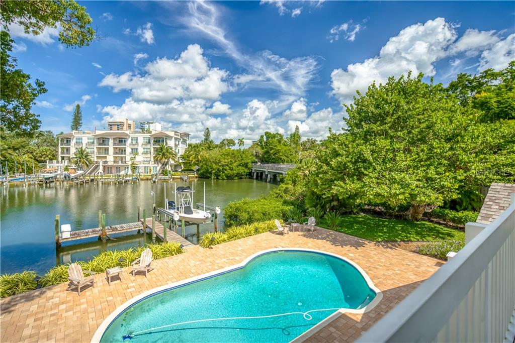 View of Expansive Lanai, Free-Form Saltwater Pool, and Hudson Bayou from the Master Bedroom Suite - Single Family Home for sale at 1595 Bay Point Dr, Sarasota, FL 34236 - MLS Number is A4479218