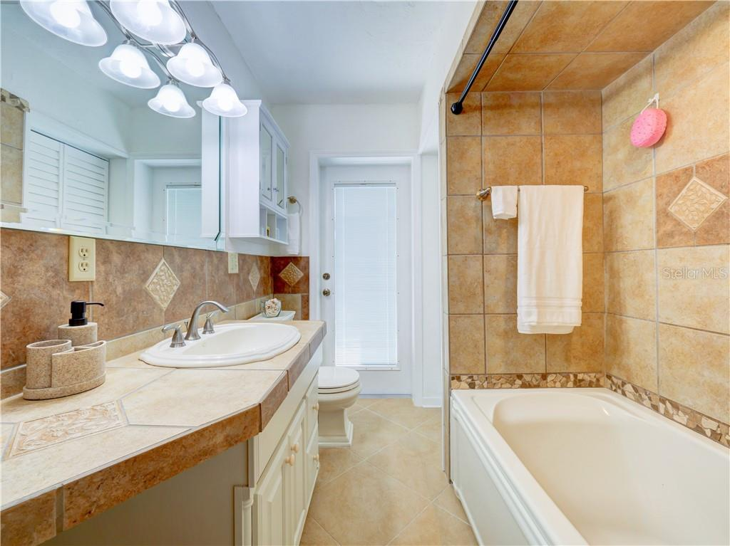 Hall Bathroom features tile counter tops, a tub with shower, a linen closet, and direct access to the back porch. - Single Family Home for sale at 2408 Riverside Dr E, Bradenton, FL 34208 - MLS Number is A4480609