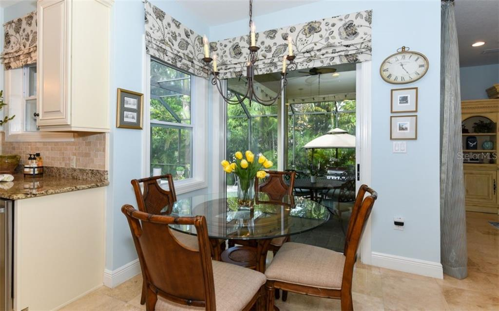 The dining space just off the kitchen features a large window and six foot sliding glass door to one of two covered lanais - Single Family Home for sale at 1603 Landfall Dr, Nokomis, FL 34275 - MLS Number is A4480987