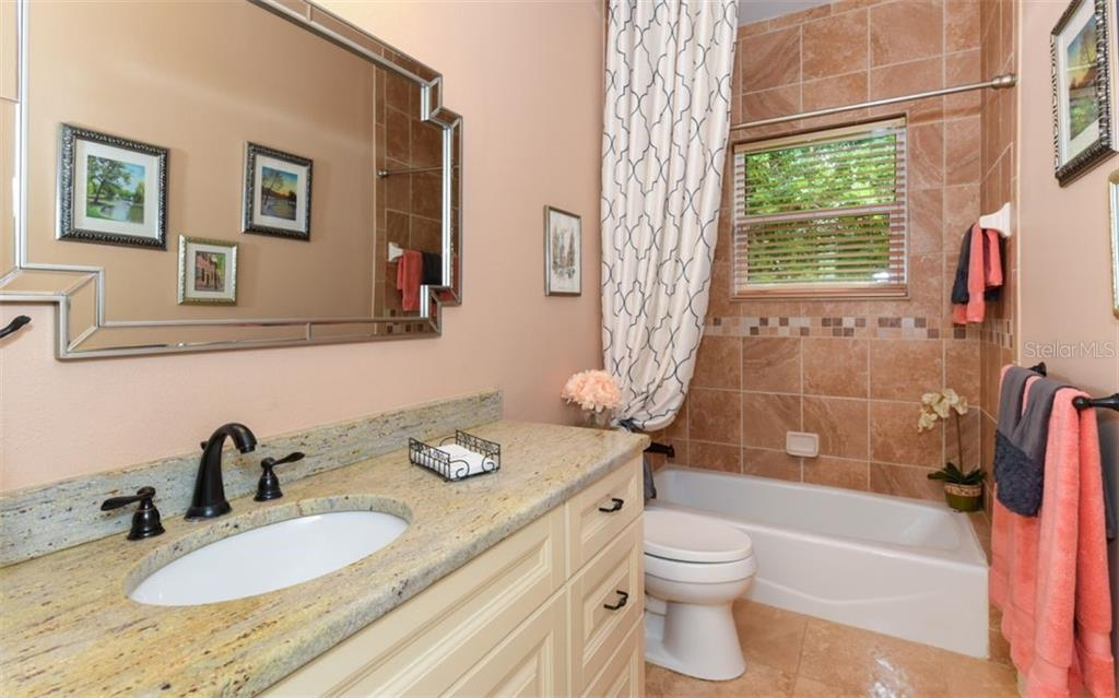 The second full bath is located near the second and third bedrooms and creates a private oasis for guests. This updated bath offers solid wood cabinetry and granite countertops. - Single Family Home for sale at 1603 Landfall Dr, Nokomis, FL 34275 - MLS Number is A4480987