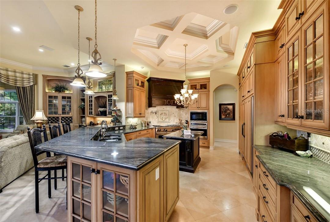 Custom eat in kitchen , a long breakfast bar with special bubble glass cabinetry for all your pretty collectibles - Single Family Home for sale at 8263 Archers Ct, Sarasota, FL 34240 - MLS Number is A4483993