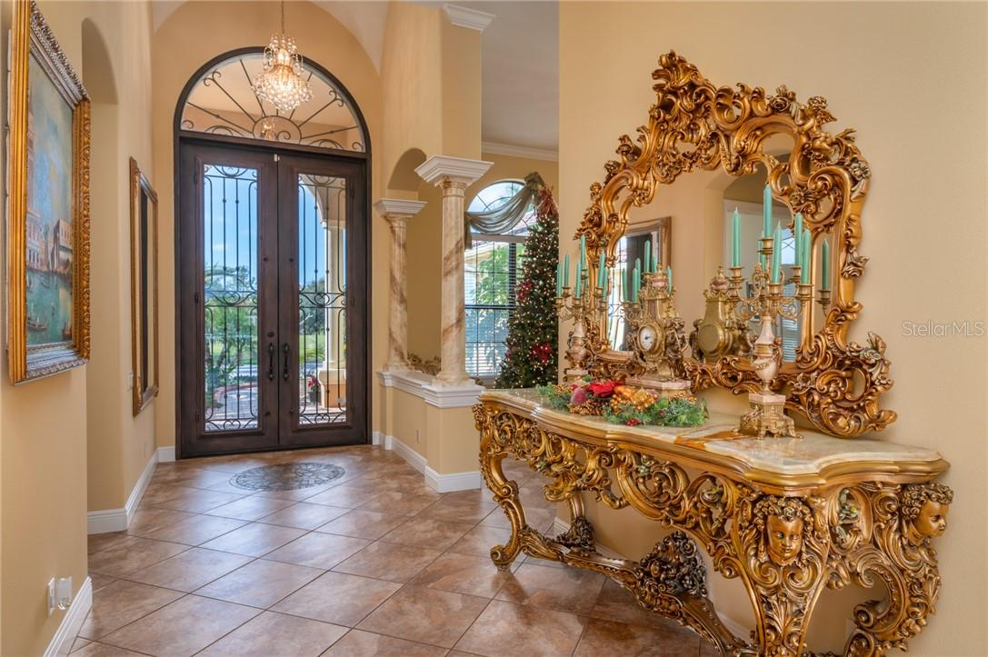 Front Foyer with an opening to the Dining Room to the right in this photo, set off by the faux marble columns between the Dining Room and Entry Foyer. - Single Family Home for sale at 11720 Rive Isle Run, Parrish, FL 34219 - MLS Number is A4486302