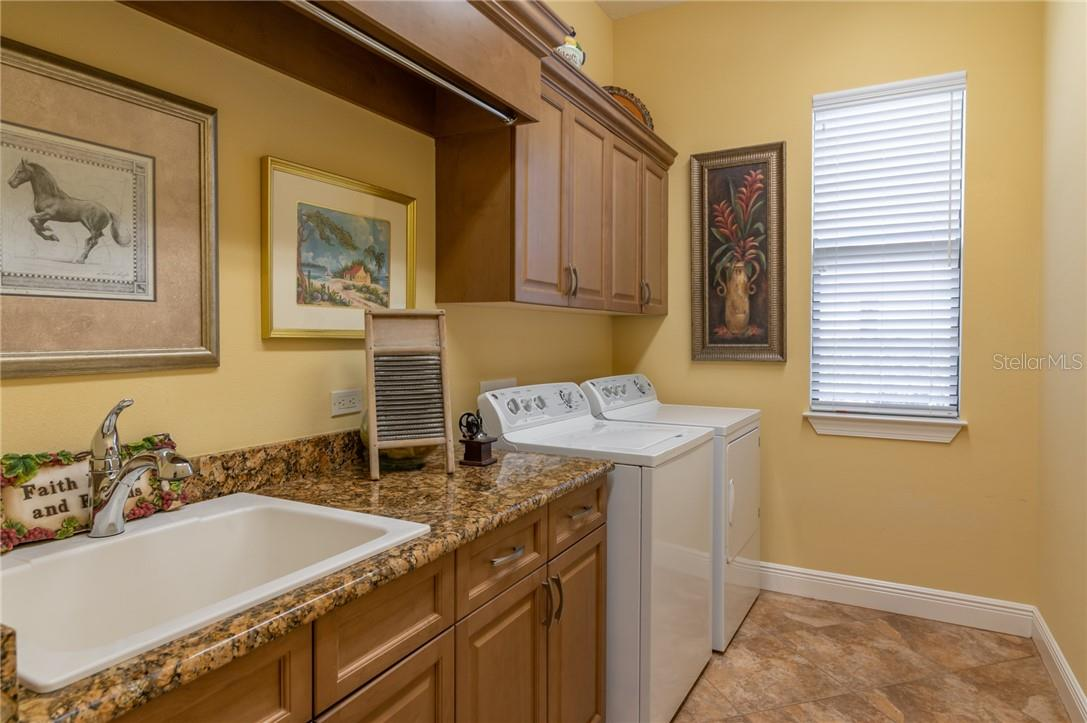 The Laundry Room is large with plenty of cabinets above the Washer and Dryer, a base cabinet with sink, granite countertops with plenty of room for folding. - Single Family Home for sale at 11720 Rive Isle Run, Parrish, FL 34219 - MLS Number is A4486302