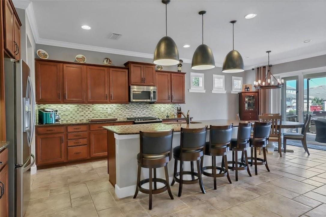 Island snack bar - look at this huge kitchen and cafe area. - Single Family Home for sale at 11713 Blue Hill Trl, Bradenton, FL 34211 - MLS Number is A4490622