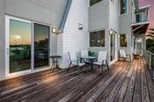 Back deck at twilight - Single Family Home for sale at 7130 Longboat Dr E, Longboat Key, FL 34228 - MLS Number is A4418105