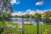 Past the wrought iron fenced in yard is a spring fed lake with bird sanctuary - Single Family Home for sale at 1522 N Lake Shore Dr, Sarasota, FL 34231 - MLS Number is A4442286
