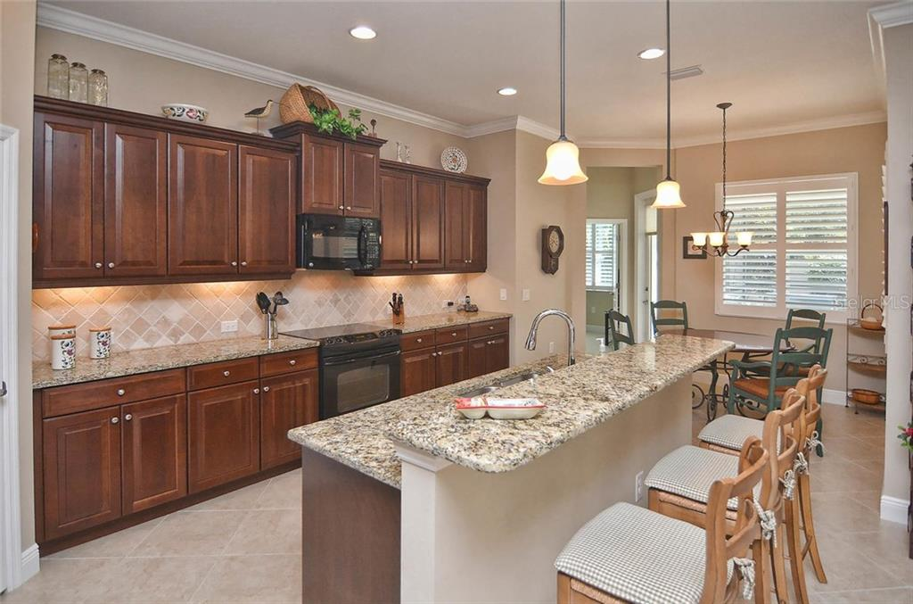 Kitchen to breakfast nook - Single Family Home for sale at 293 Marsh Creek Rd, Venice, FL 34292 - MLS Number is N5914238