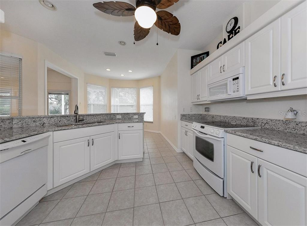 Kitchen to breakfast nook - Single Family Home for sale at 2196 Calusa Lakes Blvd, Nokomis, FL 34275 - MLS Number is N5915879