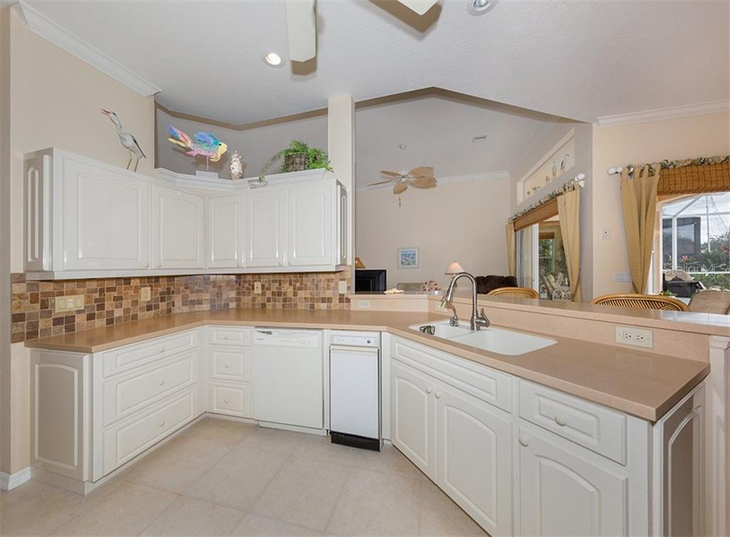 Kitchen to living room - Single Family Home for sale at 627 Lakescene Dr, Venice, FL 34293 - MLS Number is N6103268
