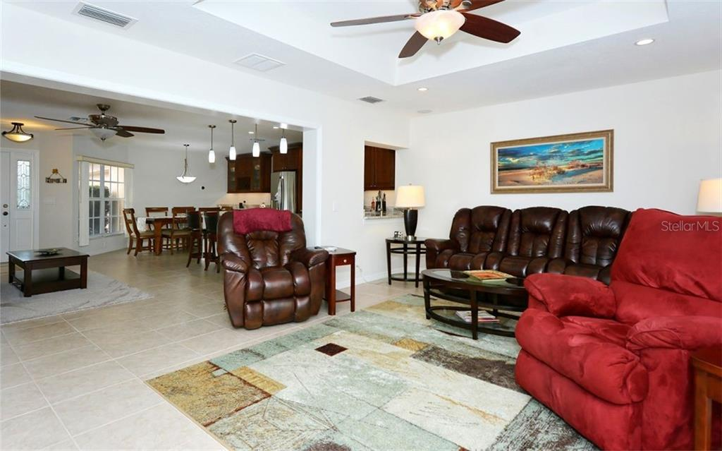 Family room to living room and dining room - Single Family Home for sale at 1460 Strada D Argento, Venice, FL 34292 - MLS Number is N6104612