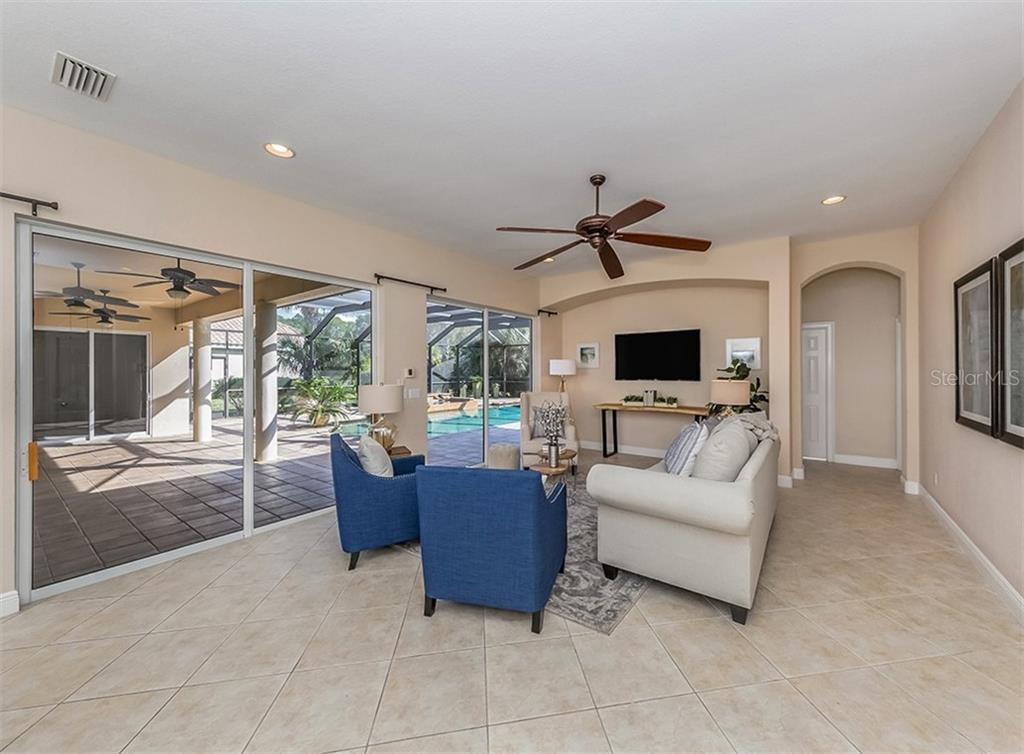 Family room with sliders to lanai/pool - Single Family Home for sale at 106 Vicenza Way, North Venice, FL 34275 - MLS Number is N6106168
