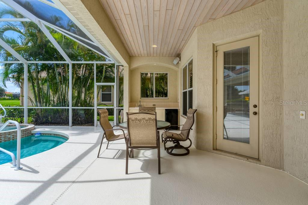 One of two under roof lounge areas. Note, ceiling panels and wet bar - Single Family Home for sale at 601 Cockatoo Cir, Venice, FL 34285 - MLS Number is N6111658