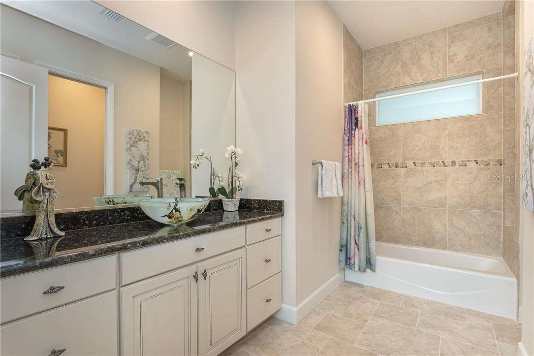 Guest bath one, with tub/shower combination. - Single Family Home for sale at 1670 Maria St, Englewood, FL 34223 - MLS Number is N6113779