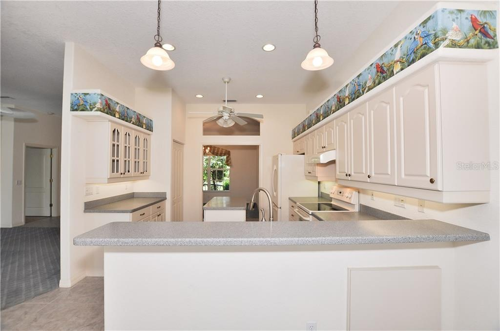 Kitchen Breakfast Bar With Pendant Lighting. The Kitchen Has Corian Counter  Tops And A Kitchen