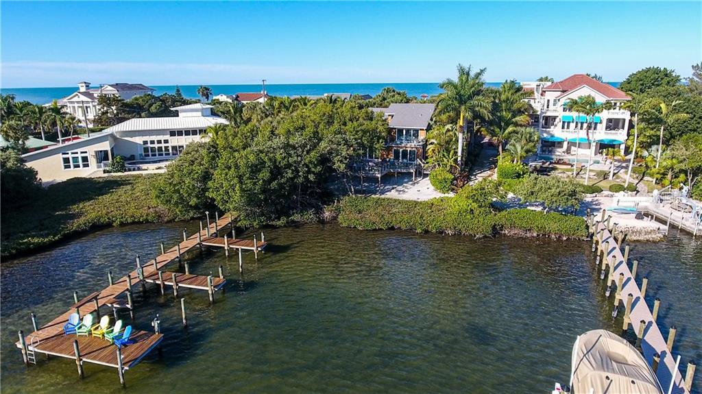 View of the rear elevation of the home with the deeded dock on the left. - Single Family Home for sale at 140 N Casey Key Rd, Osprey, FL 34229 - MLS Number is T3228618