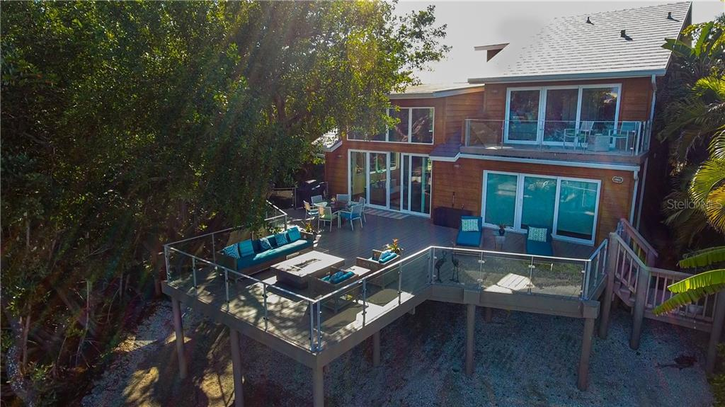 Rear elevation of home with expansive deck.  Living room sliders to the left, Master bedroom sliders on lower level to the right and guest suite on second floor above master - Single Family Home for sale at 140 N Casey Key Rd, Osprey, FL 34229 - MLS Number is T3228618