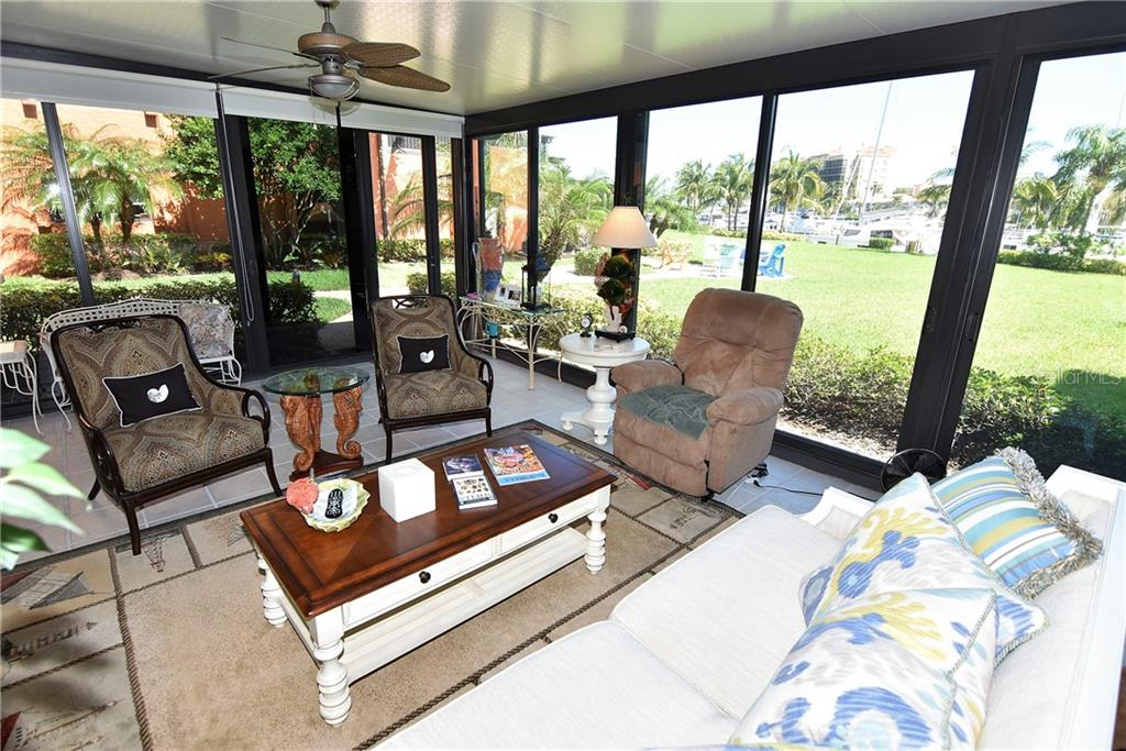 Lanai has a door in the corner allowing access to the Marina as well as a sitting area complete with Adirondack chaits - Condo for sale at 3210 Southshore Dr #11a, Punta Gorda, FL 33955 - MLS Number is C7402449