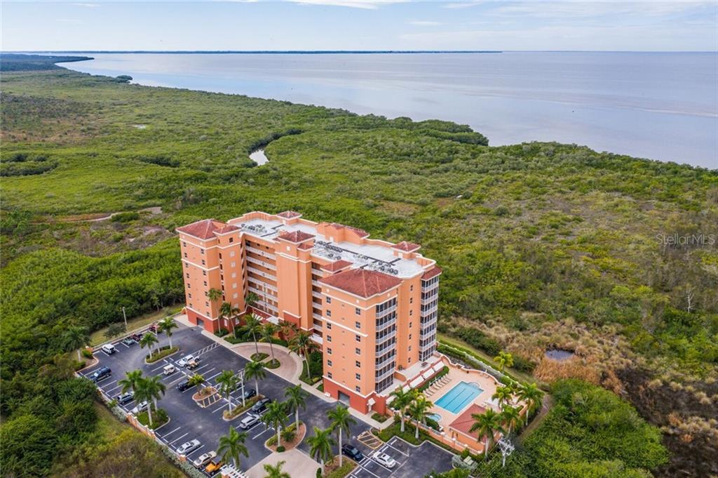 Aerial view of Vista Del Sol, pool, and Charlotte Harbor - Condo for sale at 3191 Matecumbe Key Rd #705, Punta Gorda, FL 33955 - MLS Number is C7423322