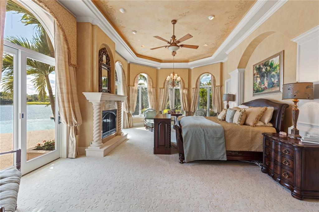 Expansive master suite bedroom with gas fireplace, an extra side room on the end, and luxurious views of the backyard terrace. - Single Family Home for sale at 7320 Barclay Ct, University Park, FL 34201 - MLS Number is A4200908