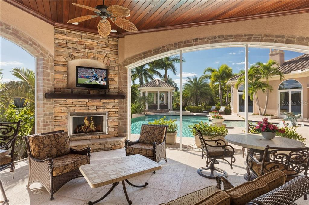 Fully equipped summer kitchen with gas fireplace, television and plenty of space to relax! - Single Family Home for sale at 7320 Barclay Ct, University Park, FL 34201 - MLS Number is A4200908