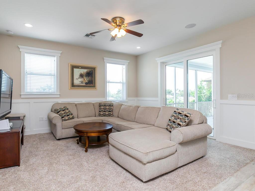 Upstairs family room with kitchenette, sliders to patio overlooking the water and pool - Single Family Home for sale at 7643 Cove Ter, Sarasota, FL 34231 - MLS Number is A4403215