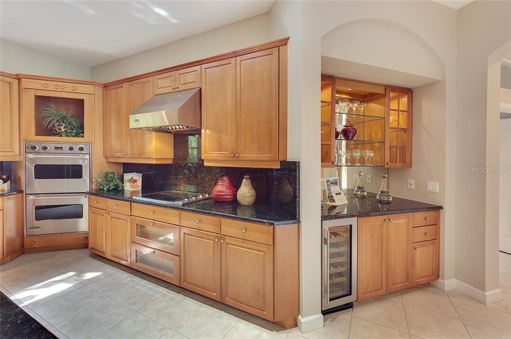Kitchen/Bar area with built-in cabinetry and wine refrigerator. - Single Family Home for sale at 2972 Jeff Myers Cir, Sarasota, FL 34240 - MLS Number is A4424133