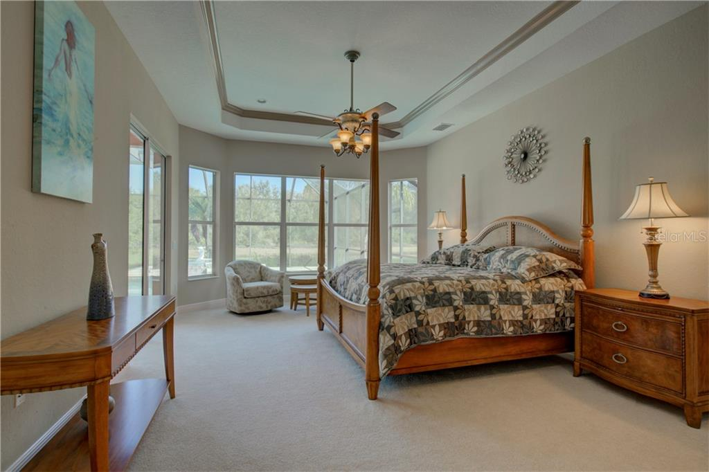 Master bedroom with lighted ceiling fan, sitting area, his and hers walk-in closets, and sliding doors that lead to the pool/spa area. - Single Family Home for sale at 15109 17th Ave E, Bradenton, FL 34212 - MLS Number is A4425963