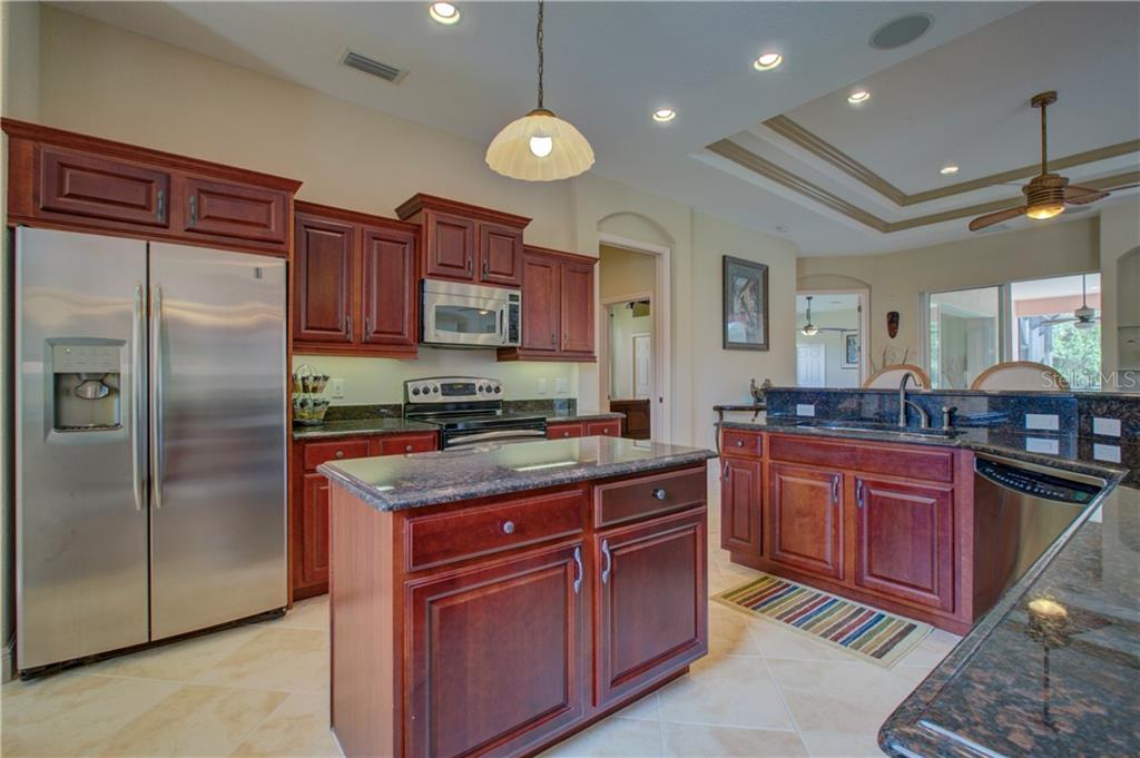 The gourmet kitchen should inspire you to create many scrumptious meals and then some, with wood cabinetry, granite countertops, under-cabinet lighting, island with storage, stainless steel appliances, closet pantry, and an amazing view of the pool/spa and lake. - Single Family Home for sale at 15109 17th Ave E, Bradenton, FL 34212 - MLS Number is A4425963