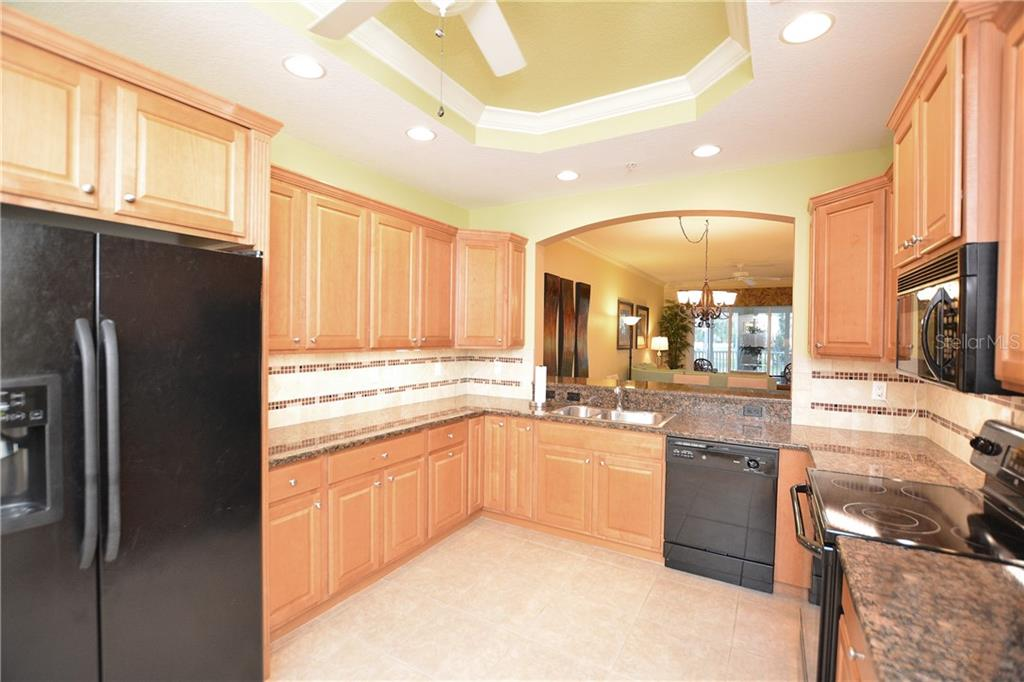 Stunning eat-in kitchen with tray ceiling, wood cabinets w/crown top molding, tile backsplash & granite countertops. - Condo for sale at 5304 Manorwood Dr #2b, Sarasota, FL 34235 - MLS Number is A4448585
