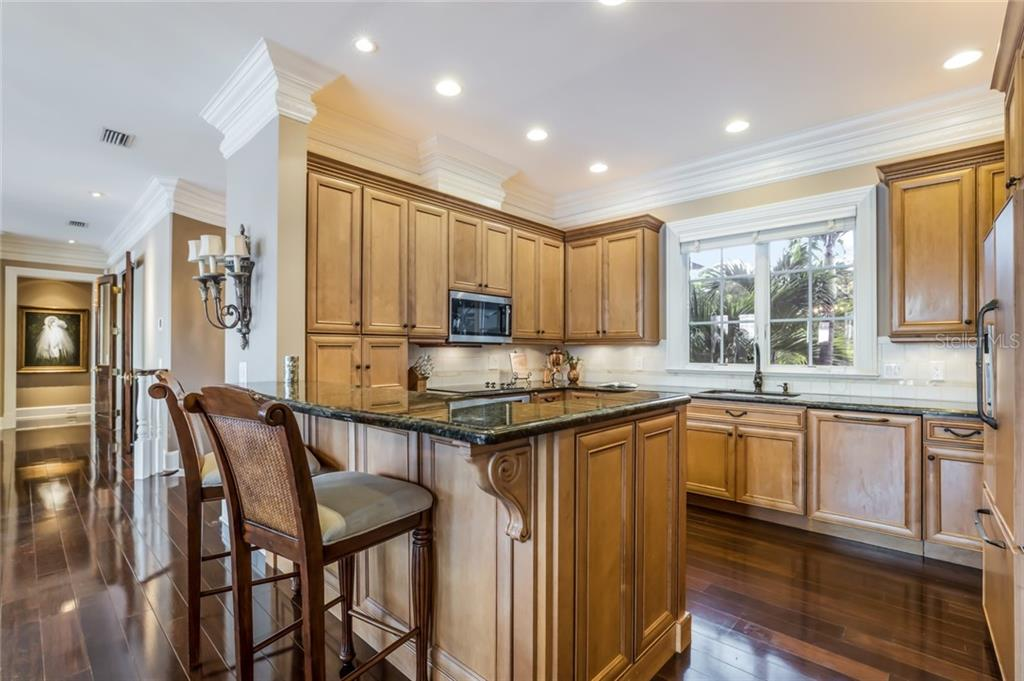 Preparing fabulous meals is a delight in this fully-equipped kitchen with granite countertops and custom soft-close cabinets with crown molding, plus under & above cabinet lighting. - Single Family Home for sale at 6438 Hollywood Blvd, Sarasota, FL 34231 - MLS Number is A4449895