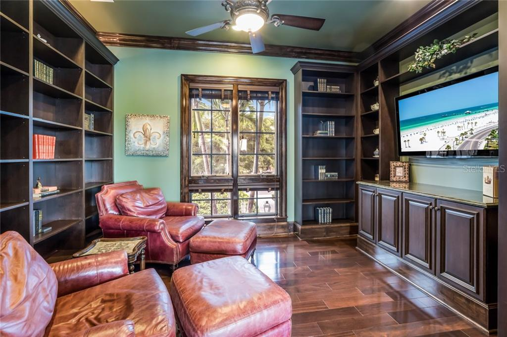 Cozy up with your favorite book or movie in the library, with custom built-in shelving and cabinets in dark rich wood tones. - Single Family Home for sale at 6438 Hollywood Blvd, Sarasota, FL 34231 - MLS Number is A4449895
