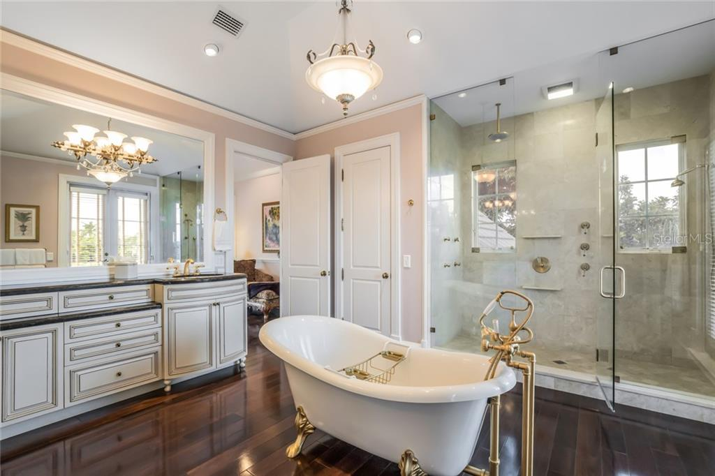 Revitalize yourself in the marble-tiled shower under the ceiling mounted rainhead and wall-mounted body sprayers. - Single Family Home for sale at 6438 Hollywood Blvd, Sarasota, FL 34231 - MLS Number is A4449895