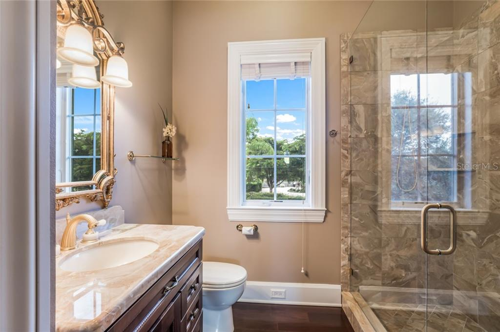 The guest suite bathroom is tastefully appointed with a marble vanity top, marble-tiled shower, and linen closet. - Single Family Home for sale at 6438 Hollywood Blvd, Sarasota, FL 34231 - MLS Number is A4449895